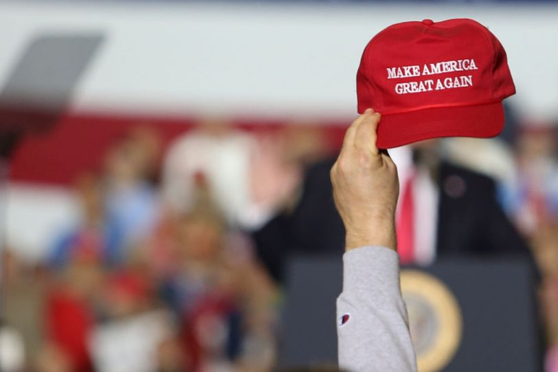 A supporter seen raising a caps writting on it 'Make America...