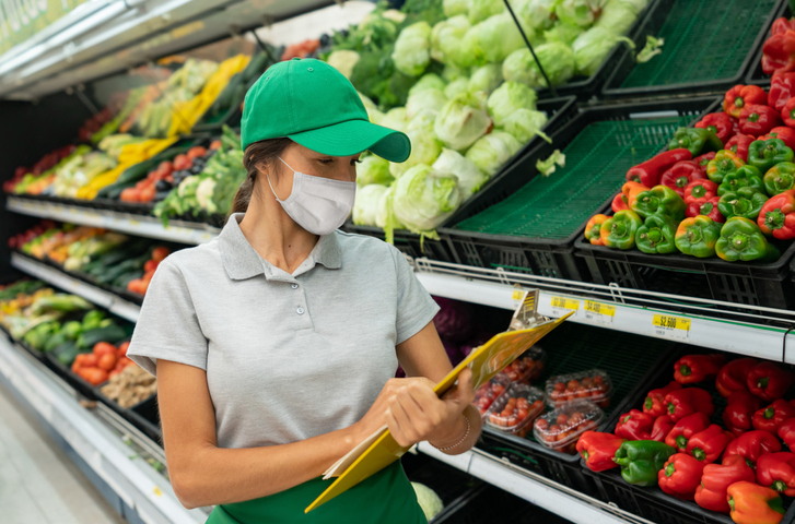 Woman wearing a facemask while working at the grocery store making the inventory